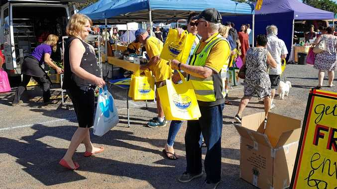 ON THE JOB: Lions Kerry Naumann and Alan Carpenter hand out the bags.