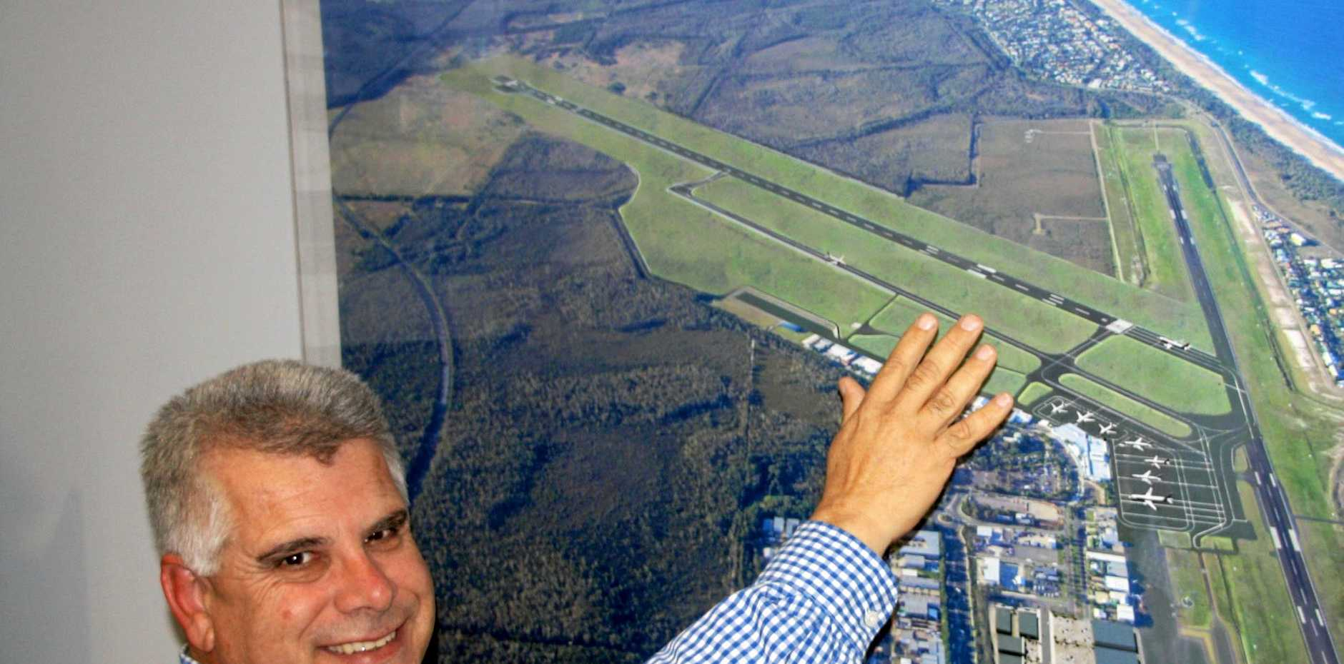 Sunshine Coast Airport CEO Peter Pallott with an artist's impression of the airport expansion which clearly shows two runways.