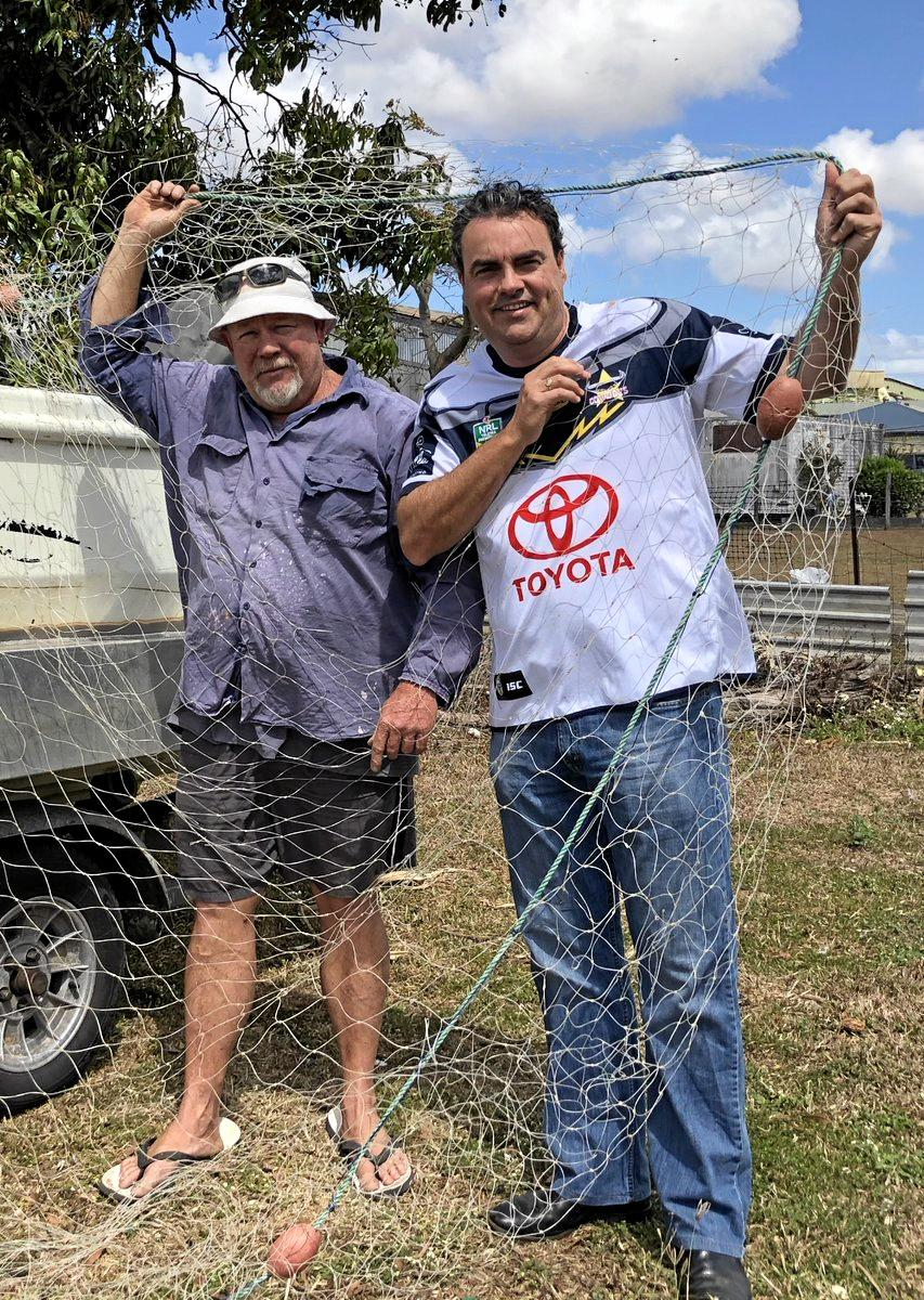 Commercial fisherman Ron Brennan and Member for Whitsunday Jason Costigan examine nets damaged by sharks in Repulse Bay. The MP has called for the shark control program to be adopted in this region.