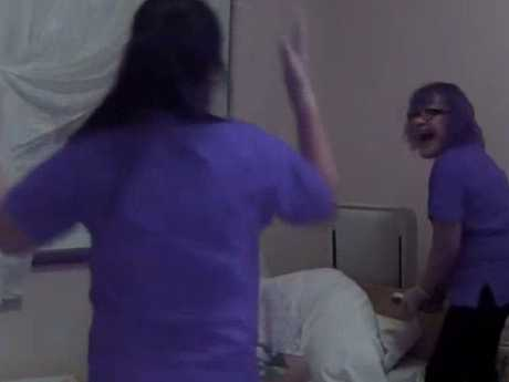 The nurse on the right is seen laughing as the other throws her hands up because Mrs Robins is getting distressed by their treatment. Picture: ABC