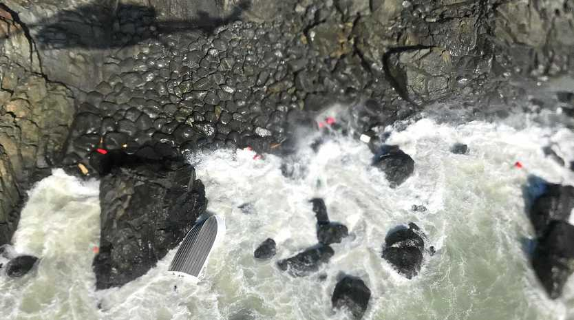 An aerial shot above rescue location shows an overturned boat and a number of bright red location devices.