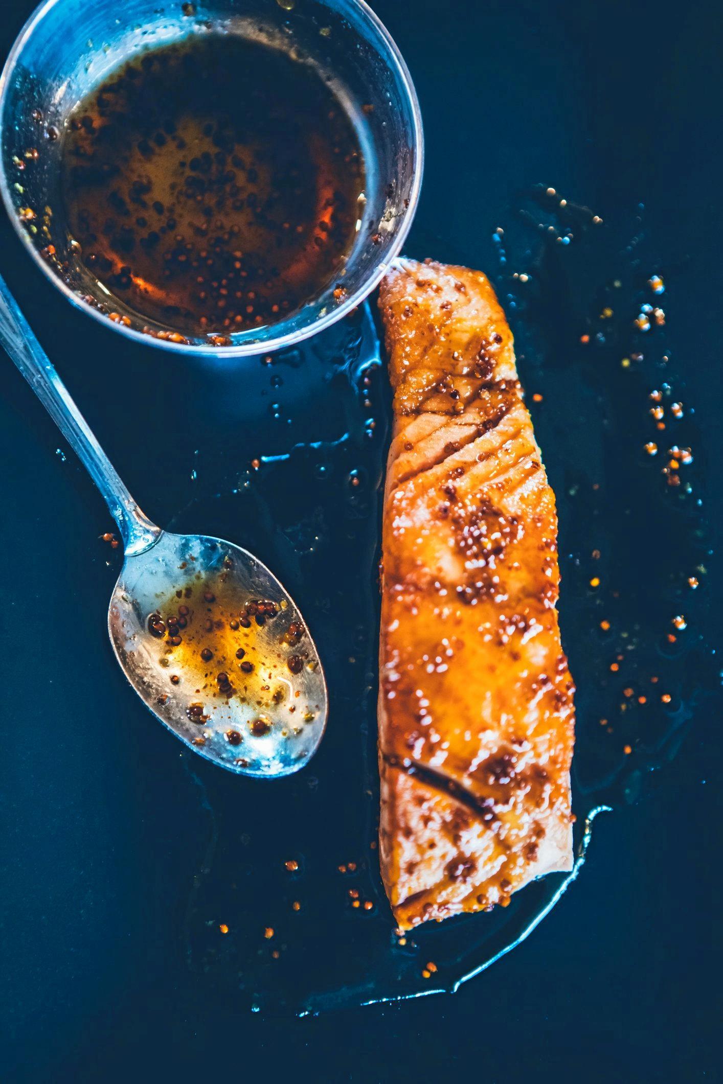 Preparing honey mustard lacquered salmon fillet.