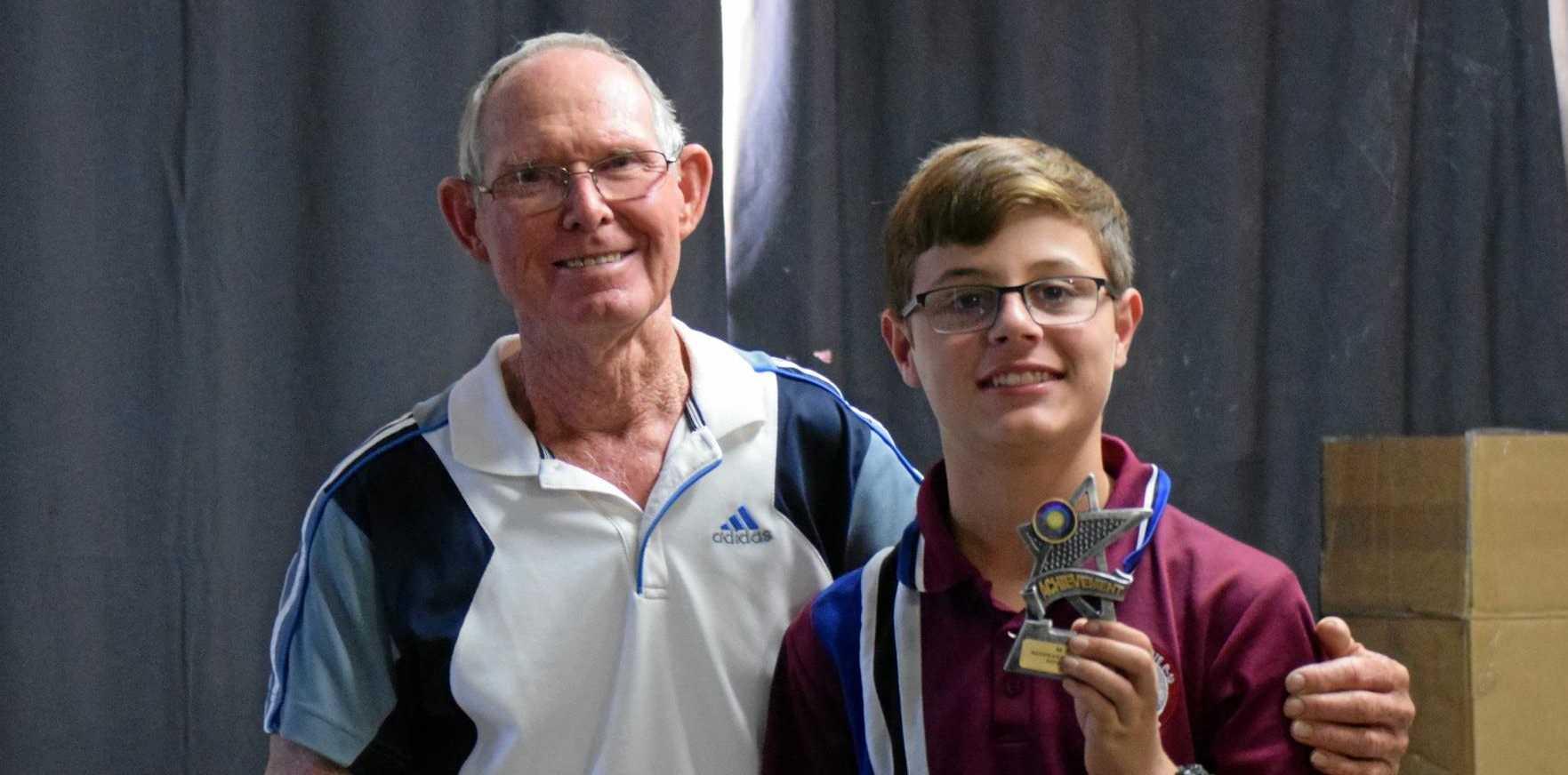 Ken Colyer presents a young Mundubbera tennis star with his award at the Mundubbera Junior Tennis awards presentation.