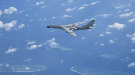 A Chinese H6K strategic bomber flies over disputed coral reefs in the South China Sea. Beijing is looking for similar island bases in the Indian and Pacific Oceans. Picture: Xinhua