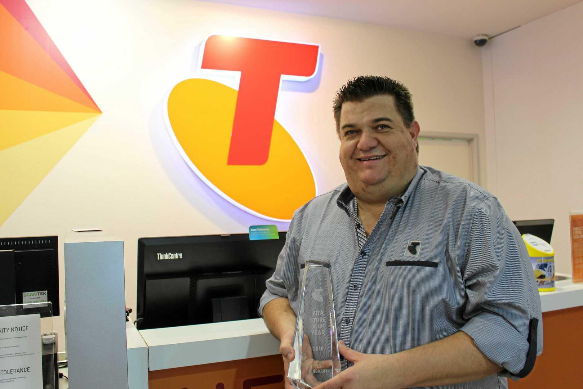 Telstra Manager Jason Koy holding the Vita Store of the Year award