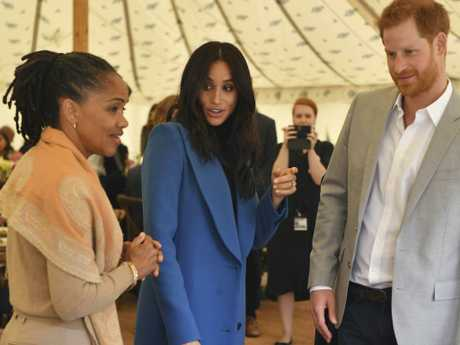 Meghan, the Duchess of Sussex, centre, talks to her mother Doria Ragland, with Prince Harry at right, as they attend a reception for the cookbook