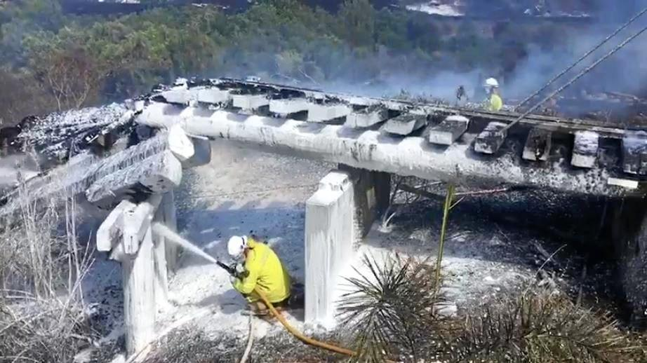 Firefighters spray a bridge at Woolooga that could not be saved, just meters from a house.
