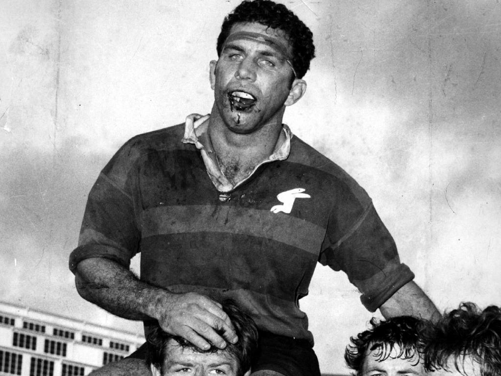 John Sattler is chaired from the field with his broken jaw.