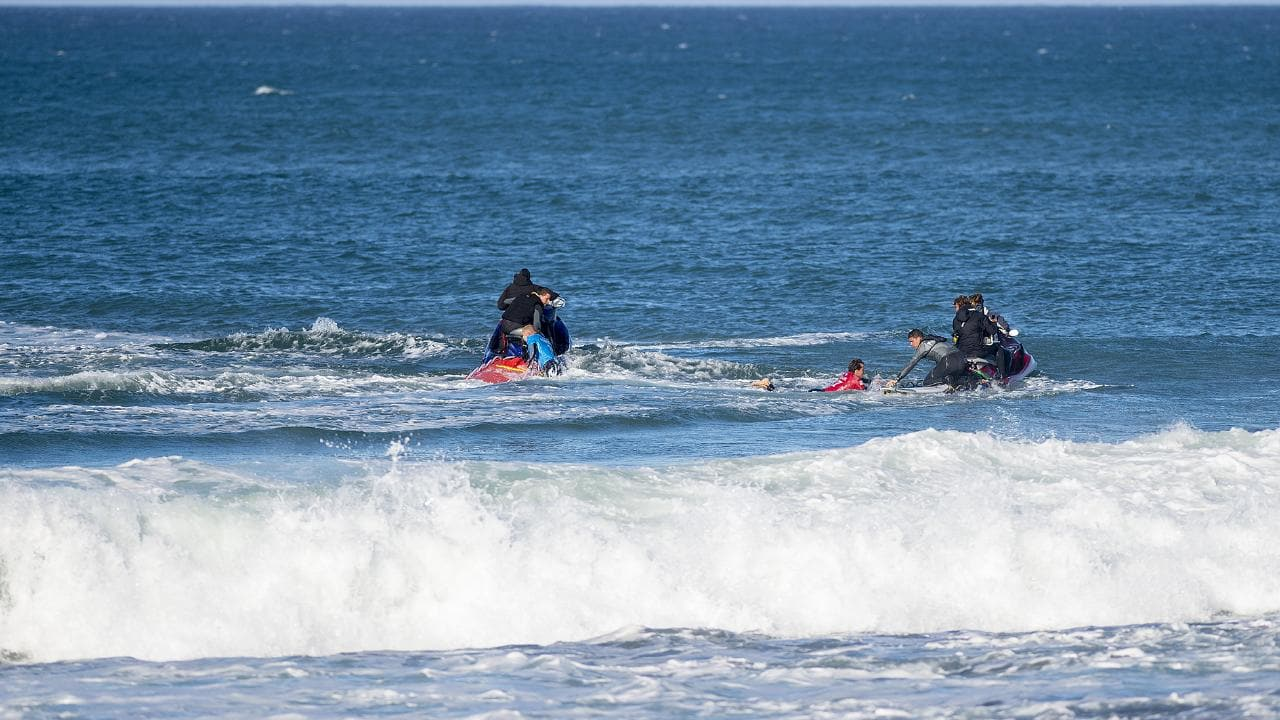 Mick Fanning of Australia (blue) and Julian Wilson of Australia (red) climbing to safety after a shark attack on Fanning at the J-Bay Open in Jeffreys Bay, South Africa on Sunday July 19, 2015. Picture: Kirstin Scholtz/World Surf League.