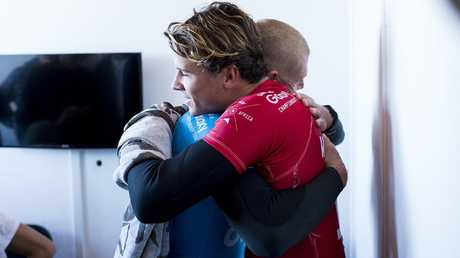 Julian Wilson hugs Mick Fanning (Blue) on shore after Fanning was attacked by a shark during the Final of the J-Bay Open in 2015. Picture: Kirstin Scholtz/World Surf League.