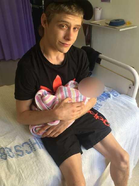 Matthew Leuthwaite holds a baby in 2015.