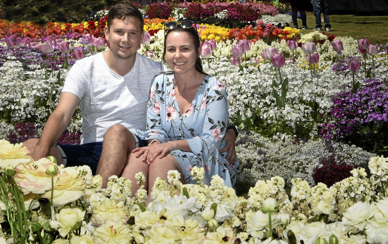 IN BLOOM: Kieran Denton and Madison Elliott sit amongst the flowers at Queens Park on Saturday.