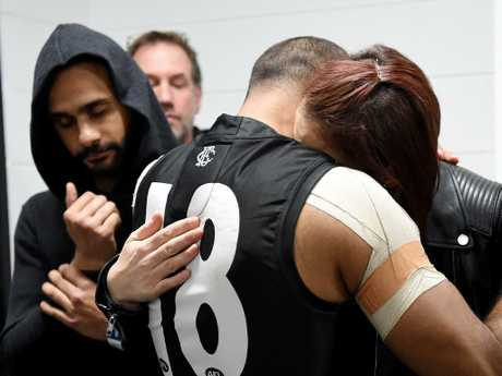 Travis Varcoe is comforted by loved ones. Picture: Nicole Garmston