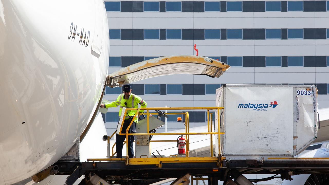 An airline worker loads a Malaysia Airlines jet at Sydney International Airport. Picture: AAP Image/Jordan Shields