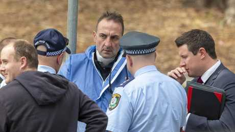 A police officers reports after examining the body. Picture: Jenny Evans