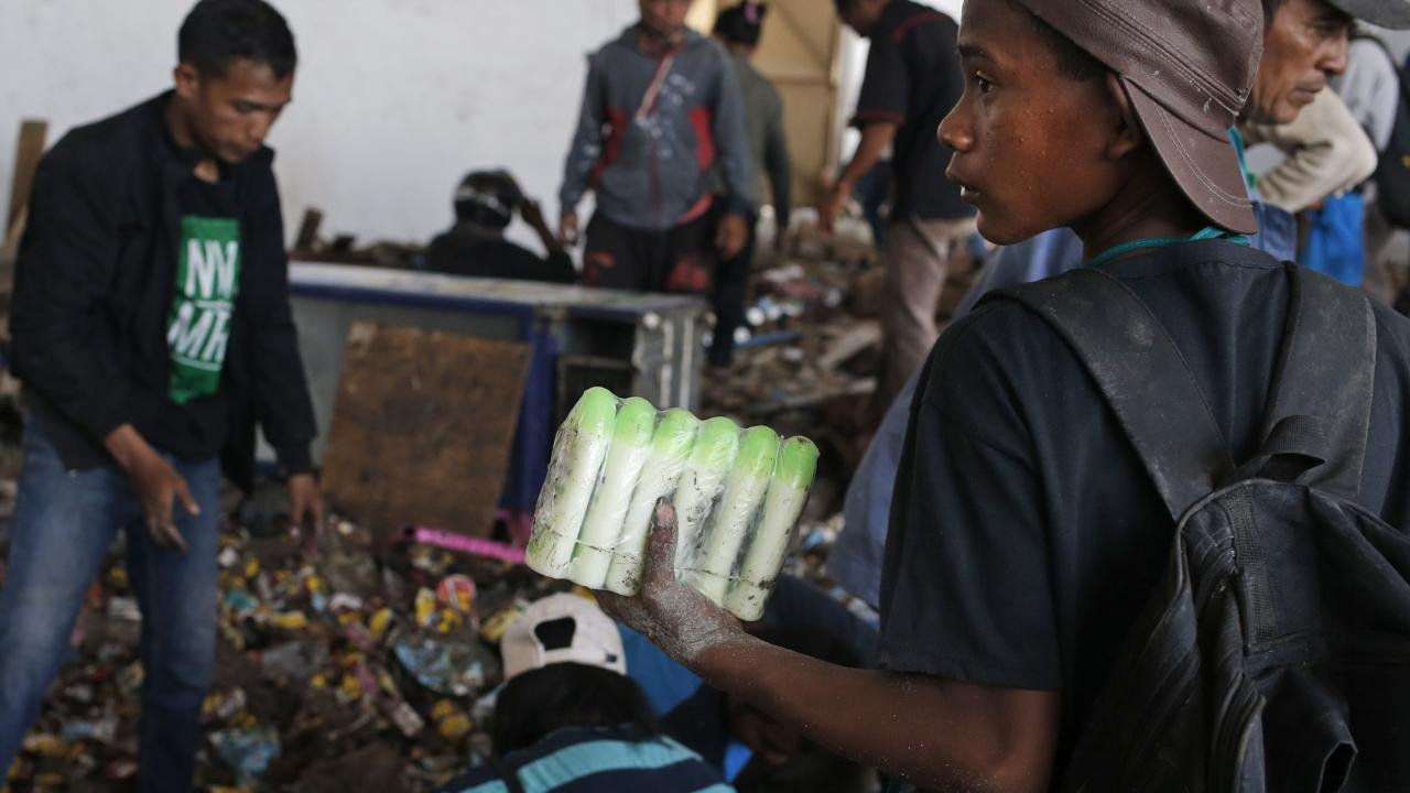 A man holds bottles of body lotion scavenged from an abandoned warehouse following an earthquake and tsunami in Palu, Central Sulawesi, Indonesia. Picture: AP Photo/Dita Alangkara