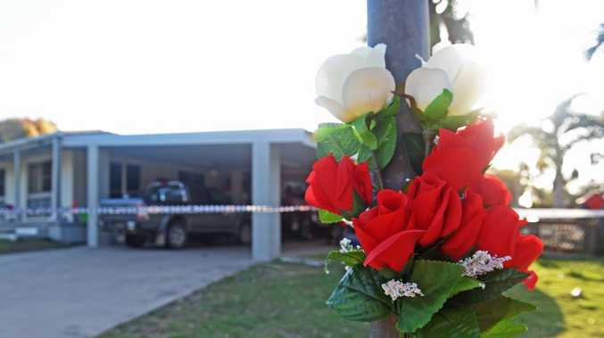 Flowers are taped to a street pole as police set up a Crime scene at Topton Street, Alva Beach after two people died. Picture: Zak Simmonds