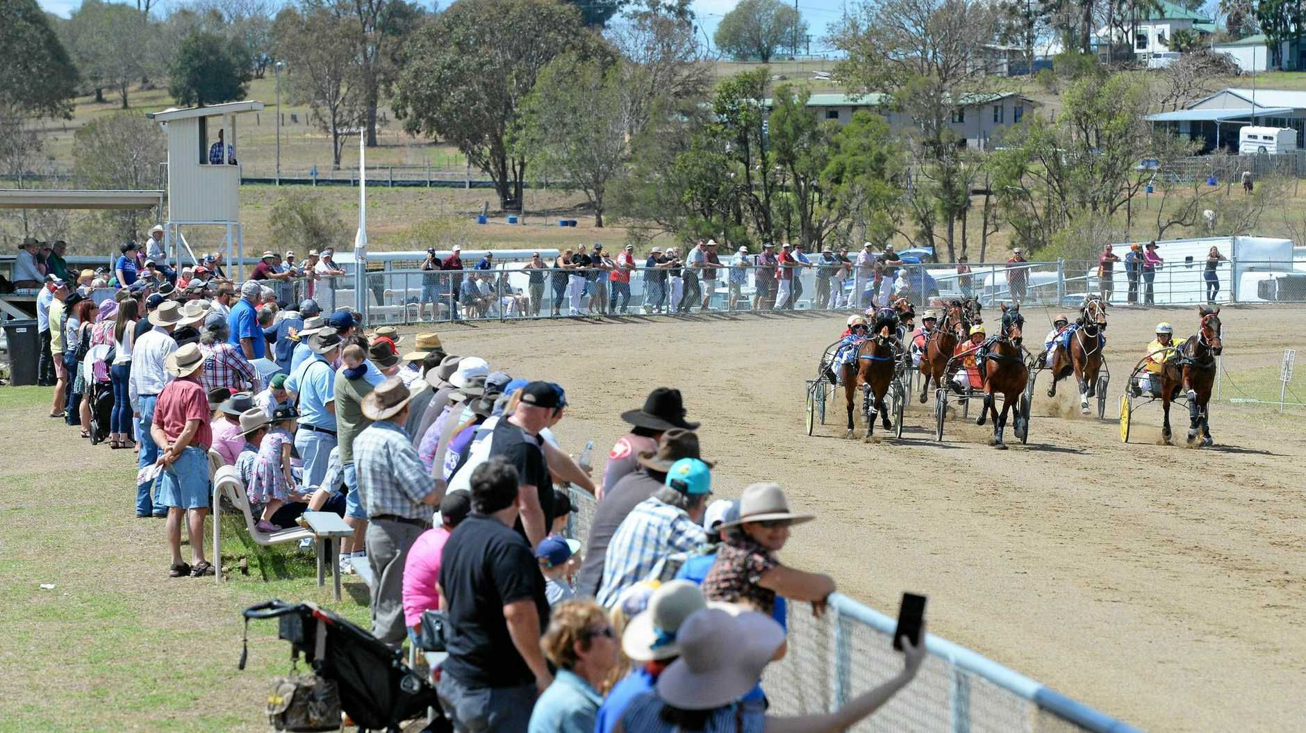 Trotting fans line the fence watching the runners at last Monday's Marburg Pacing Association TAB meeting.