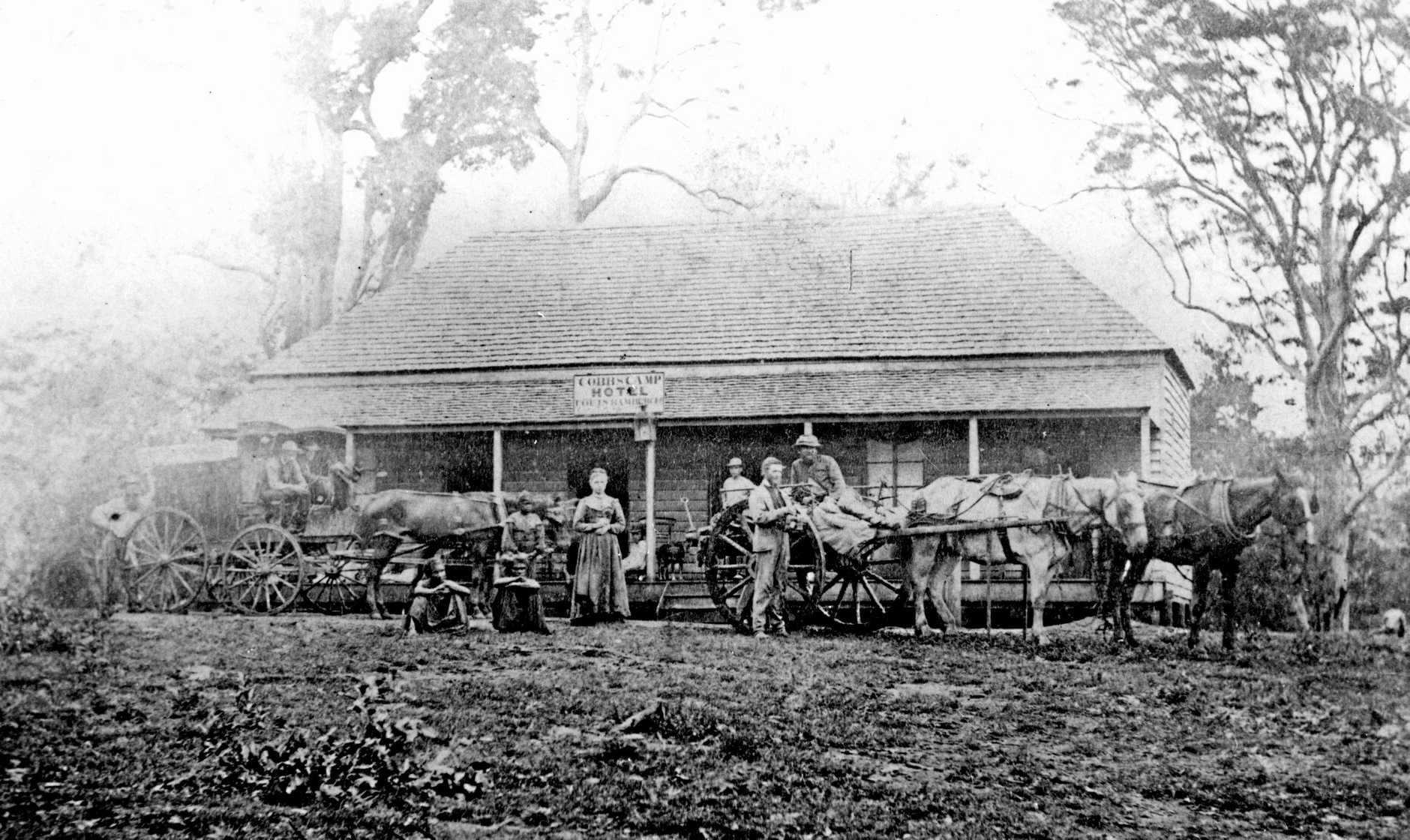 M191619 Cobb & Co. passengers and hotel staff with a coach and buggy in front of Cobb's Camp Hotel, Woombye, 1872. The hotel, together with a keeper's residence, horse stables and horse yard, was established by Cobb & Co. to provide a staging camp and accommodation for passengers following the construction of trafficable road between Brisbane and Gympie in 1868