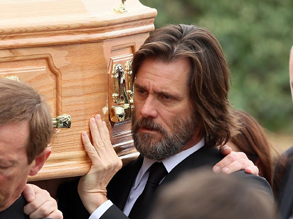 Carrey carries Ms White's coffin from her funeral service.