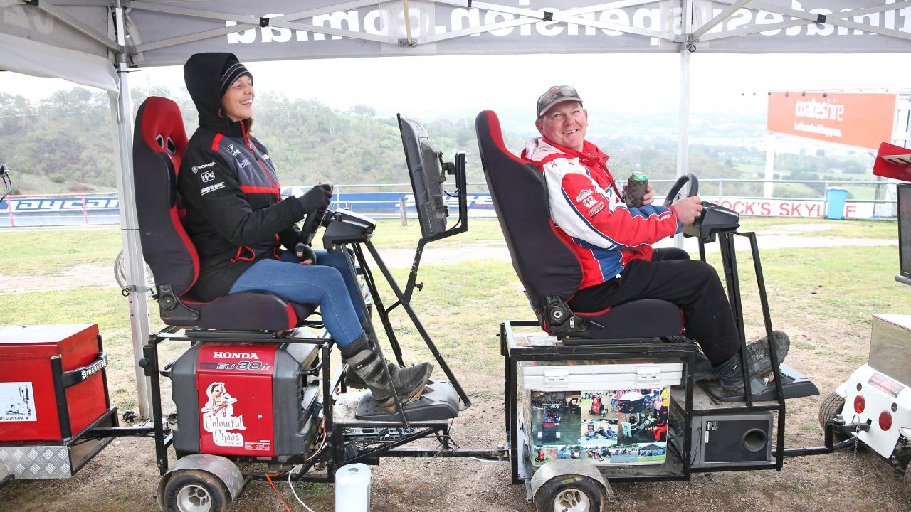 Michelle Branch and Brad Denning find time to race against each other on driving simulators attached to his mobile Esky. Picture: Richard Dobson