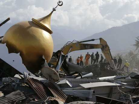 Rescuers stand beside a toppled mosque as recovery efforts continue in the earthquake-hit Sulawesi, Indonesia. The government said it was considering making devastated areas into mass graves. Picture: AP Photo/Aaron Favila