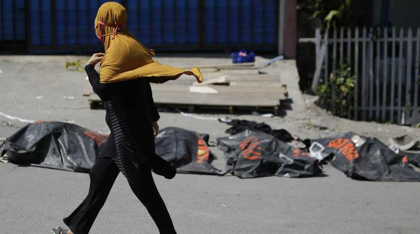 A woman walks past bodies recovered from the earthquake-hit Palu, Indonesia. The government says it is considering making devastated areas into mass graves. Picture: AP Photo/Aaron Favila