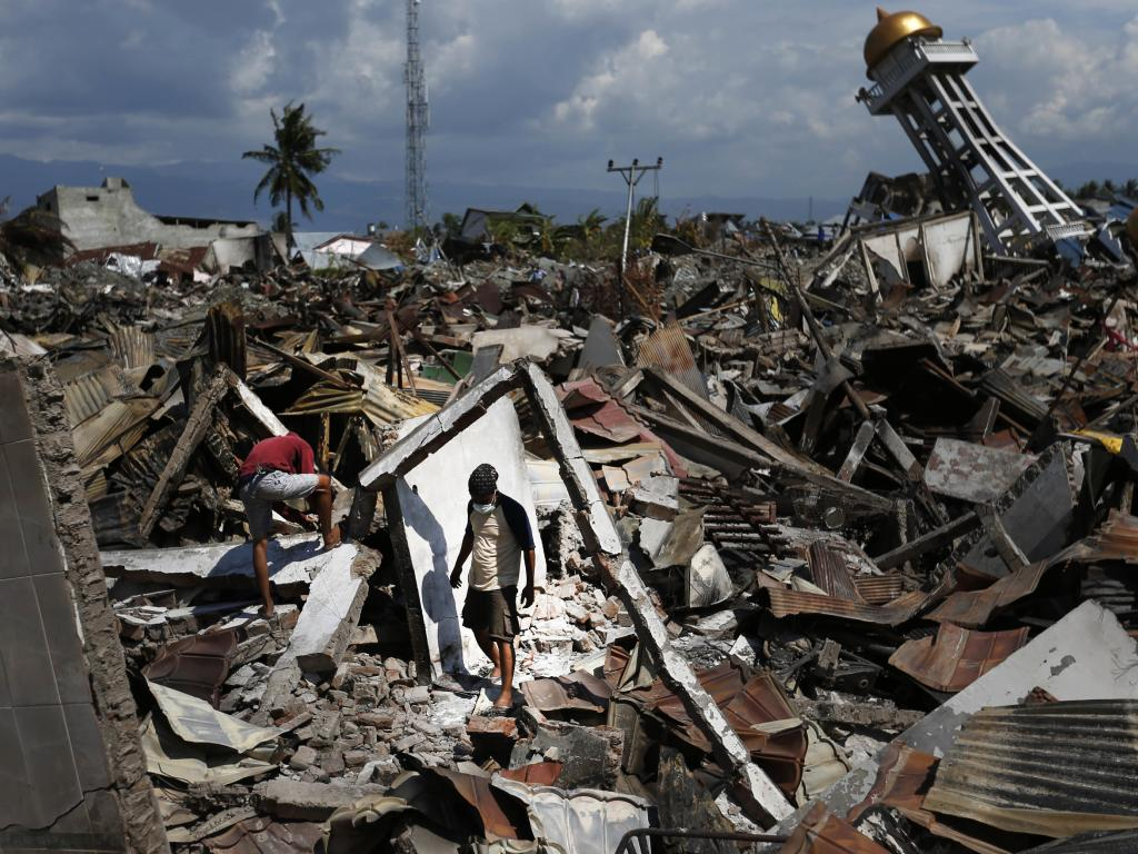Residents scavenge for usable items at the ruins in Balaroa, Indonesia, one of the hardest-hit areas. Picture: AP Photo/Dita Alangkara