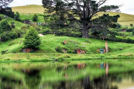 The hobbit holes at Hobbiton movie set reflecting in the small lake.