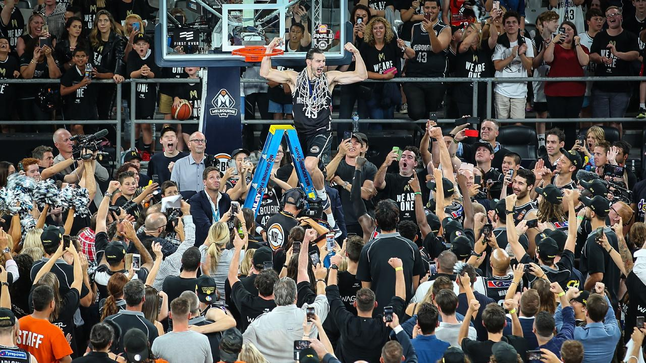 Melbourne United captain Chris Goulding celebrates with fans as he cuts down the net after winning last year's NBL Grand Final series. Pic: Getty Images