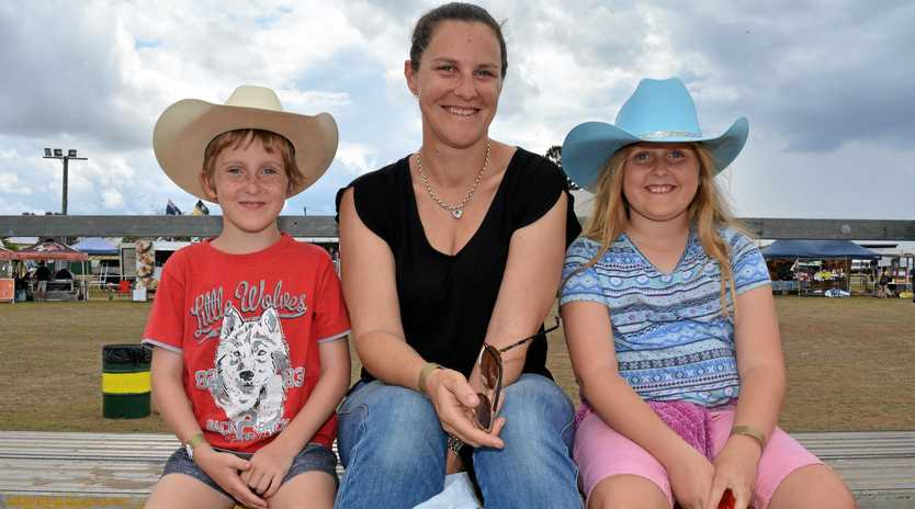 HATS ON: Chelsea, Lachlan and Michelle Howard watch the rope and tie category at the Lowood rodeo.