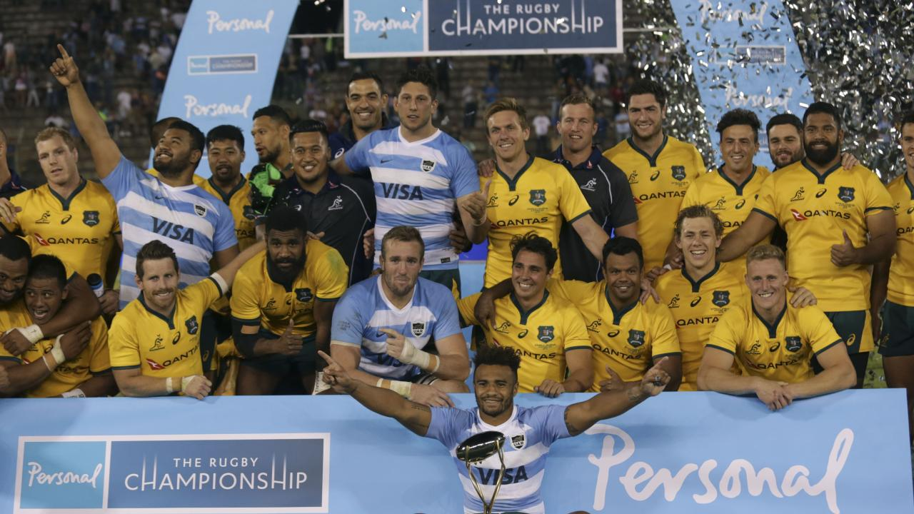 Wallabies players celebrate with the trophy after beating Argentina.