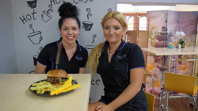 YUMMY FOOD: Cheryl-Lyn's Cafe staff Sheraya Johnson (left) and Zara Fraser cook up dozens of the popular beef burger each week.