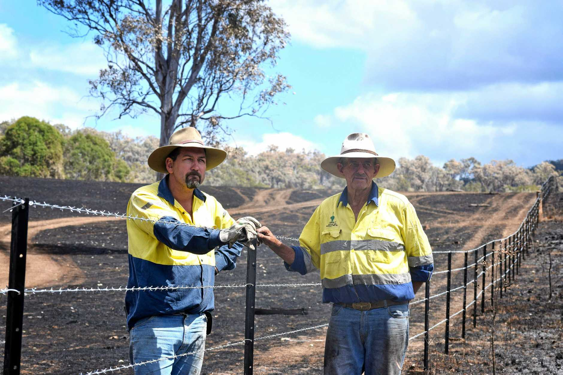 Woolooga grazier Brad Pike with father-in-law Wayne Staib at a fence newly built by volunteers after the Woolooga bushfire.