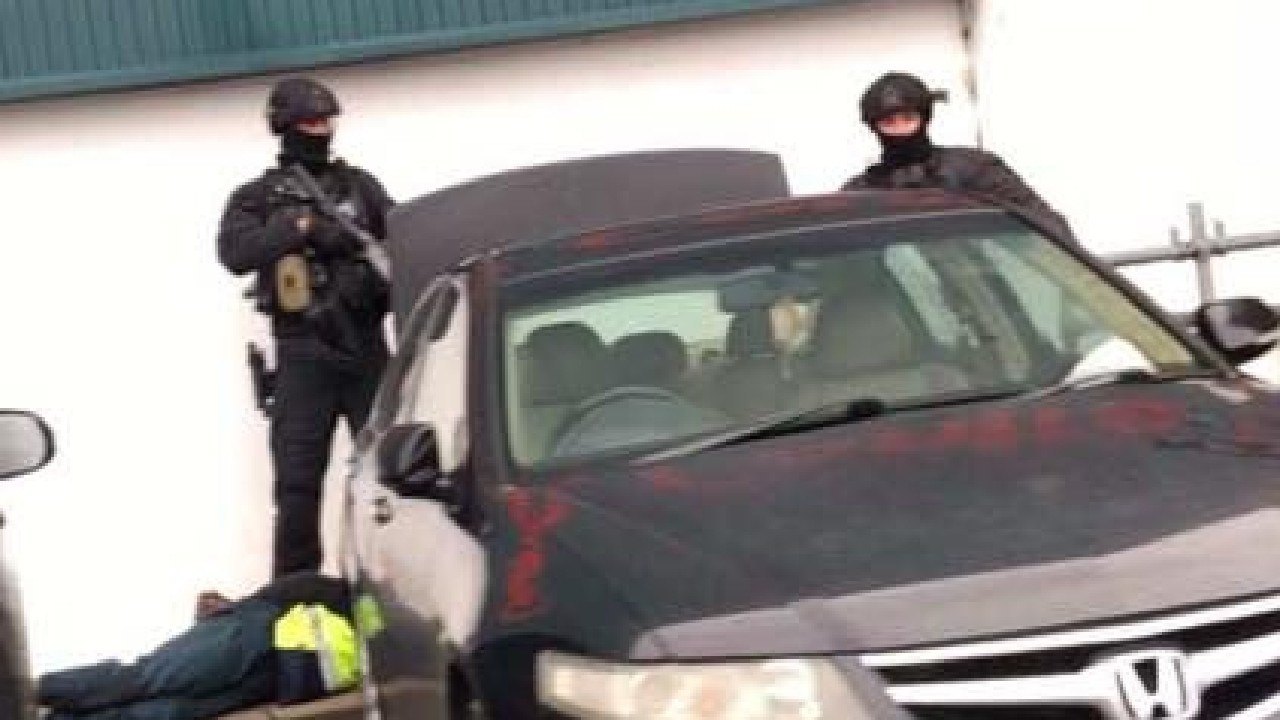 Tactical police stand over a man outside Bunnings Warehouse in Minchinbury.