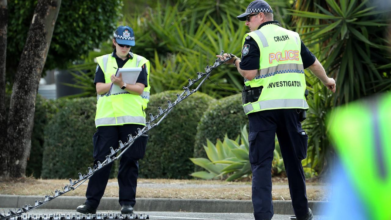 A crash investigation officer uses  a Stinger spike system at the scene of the alleged hit-and-run of police officer Peter McAulay on  Brisbane Road, Booval. Picture: Liam Kidston.