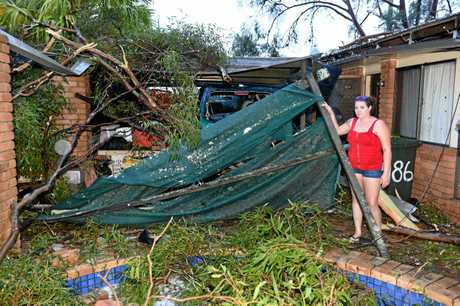 STORM DAMAGE: Shania Cameron at her grandparents' house in Maryborough, assessing the damage after a fallen tree crushed their car
