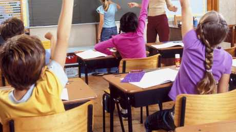 f33openday - View of children with their hands raised in class. thinkstock