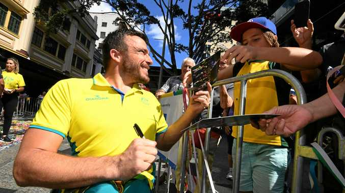 Wheelchair race gold medallist Kurt Fearnley signs autographs during a Brisbane street parade on April 27 to honour Commonwealth Games athletes. Picture: Dan Peled/AAP