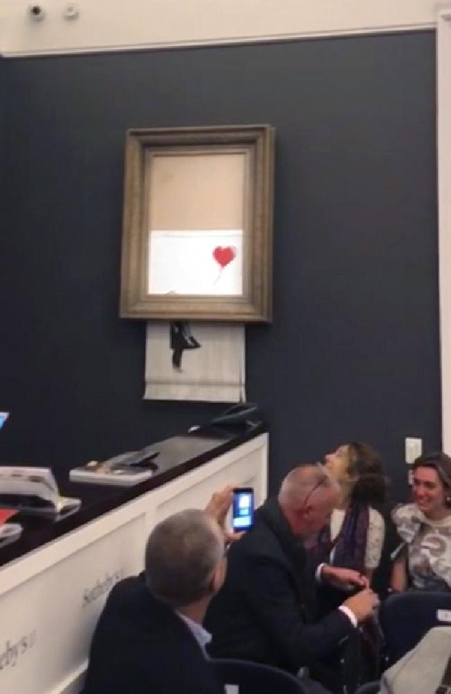People watch as the Banksy artwork is shredded at Sotheby's. Picture: Pierre Koukjian via AP