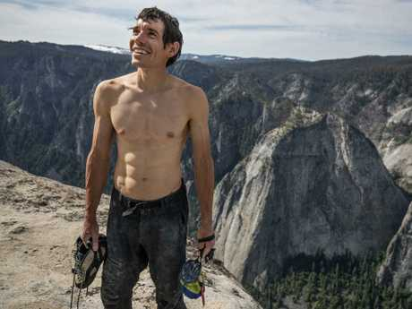 Alex Honnold holds all of his climbing gear atop the summit of El Capitan. (National Geographic/Jimmy Chin)