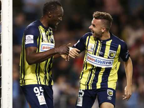 Usain Bolt celebrates with Jordan Murray after scoring his second goal.