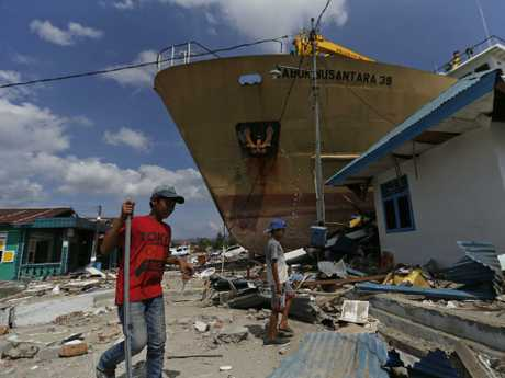 Indonesian youths walk past a ship that was swept ashore by the tsunami on the outskirts of Palu, Central Sulawesi, Indonesia. Picture: AP Photo/Dita Alangkara