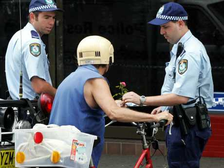 A woman hands a rose to a police officer at the scene of the murder of store owner Frank Newbery.