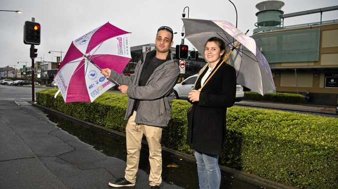 UMBRELLAS OUT: Joel Matar and Sophie Cuming in the Toowoomba CBD braving the rain.