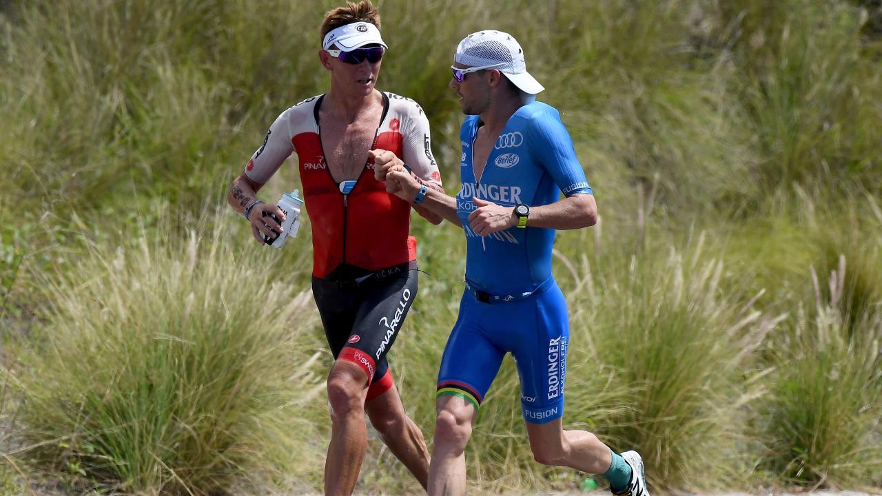 Patrick Lange (blue) passes Aussie Cameron Wurf. Picture: Getty