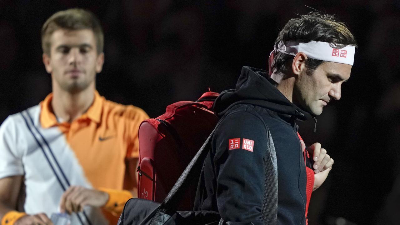 Roger Federer of Switzerland walks past Borna Coric of Croatia