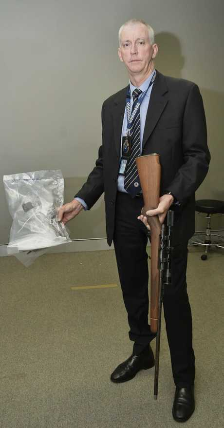 BUSTED: Toowoomba Criminal Investigation Branch Detective Senior Sergeant Paul McCusker with a hand gun and long-arm firearm seized during Operation Quebec Midway.