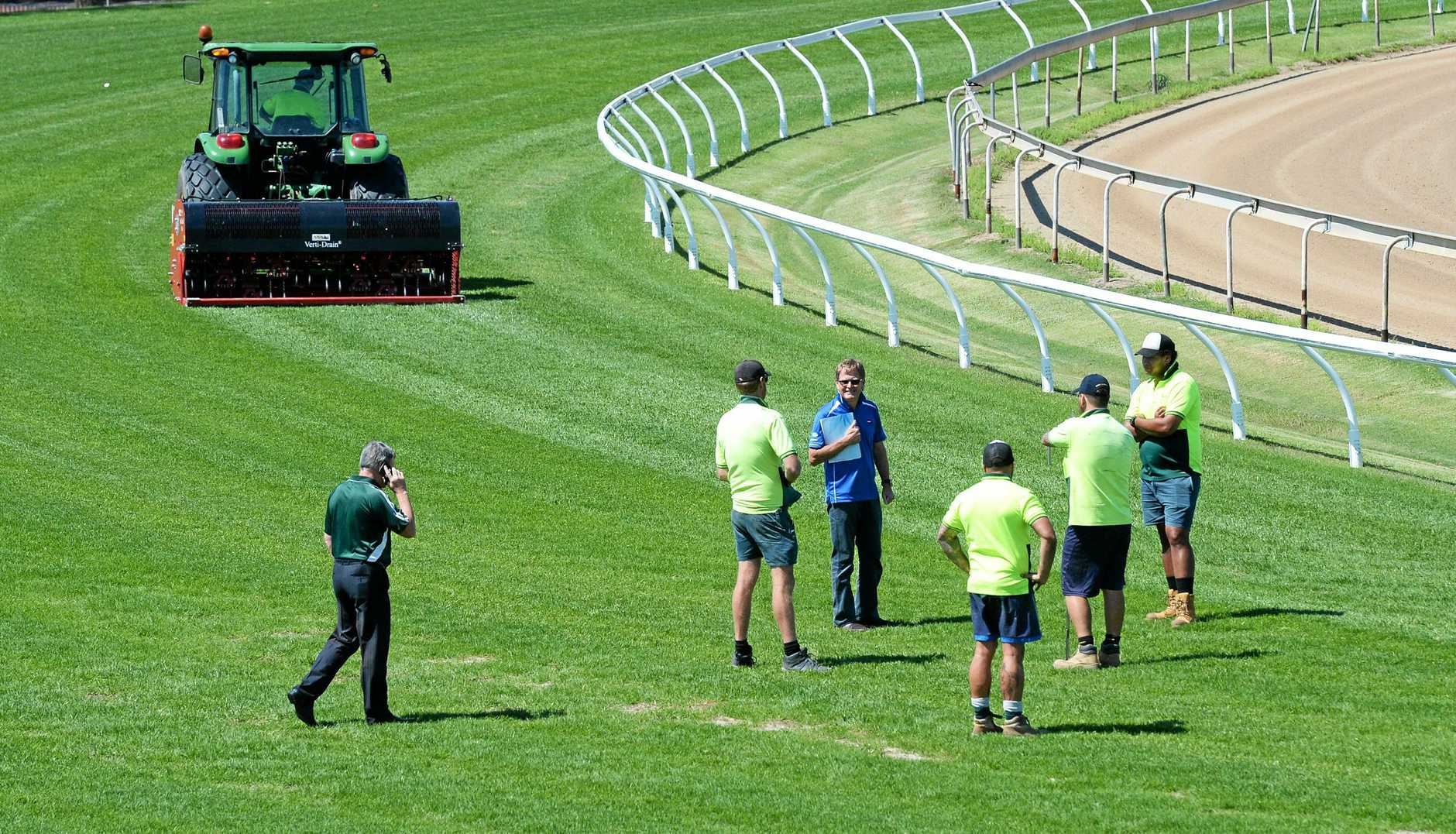 Officials on the track at the Ipswich Racetrack on October 10 after racing was abandoned.