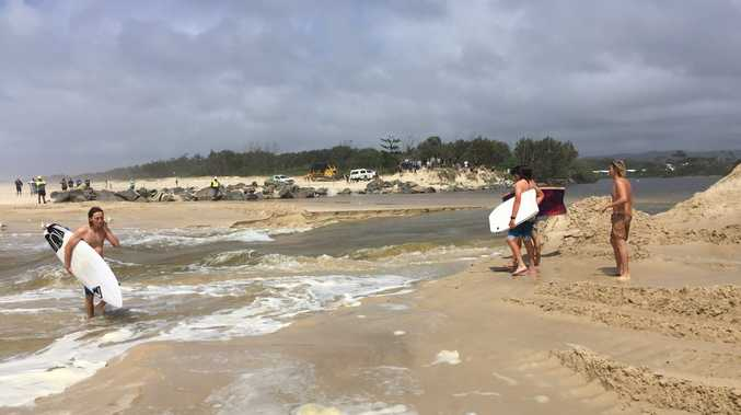 Surfers hit the wave as the mouth of Mooball Creek becomes unblocked.